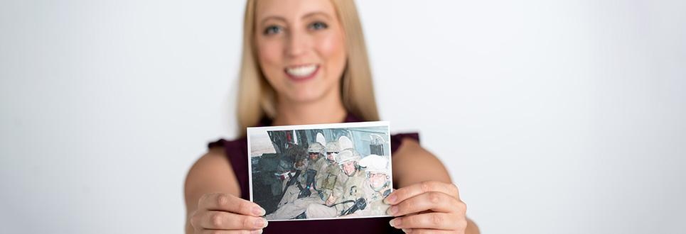 Veteran holding a photo of herself when she was deployed